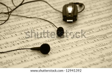 Mp3 player and earphones on a music sheet background