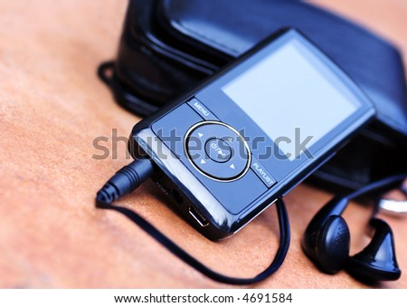 Mp3 player with earphones and cover on red background ,macro - stock photo