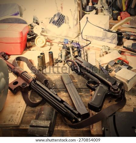 MP38 sub machine gun on the table master restorer in the interior locksmith gunsmith. instagram image retro style - stock photo