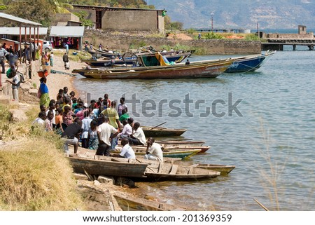 MPULUNGU, ZAMBIA - JUNE 6, 2014: Unidentified crowd of people sit in boats and wait for departure to their villages at fish harbor in Mpulungu on June 6, in Zambia 2014.  - stock photo