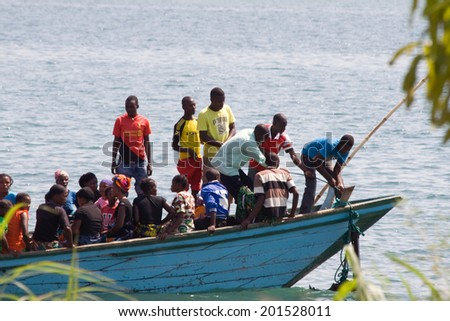 MPULUNGU, ZAMBIA - JUNE 6, 2014: Unidentified people sit in a boat, one unidentified man lifts the anchor before departure at the beach in Mpulungu on June 6, in Zambia 2014. - stock photo