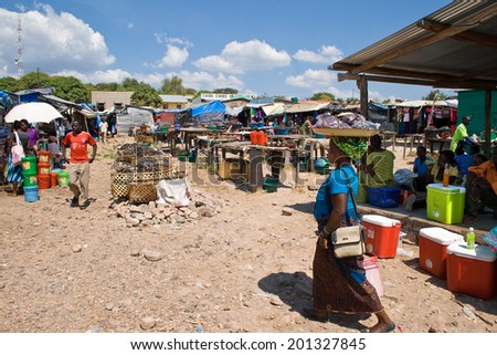 MPULUNGU, ZAMBIA - JUNE 6, 2014: Unidentified traders sell fish, sodas and other products at the fish market in Mpulungu on June 6, in Zambia 2014. One unidentified woman carries goods on her head. - stock photo