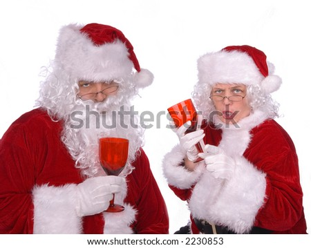 Mr. and Mrs. Claus are celebrating a good delivery with a few drinks - stock photo
