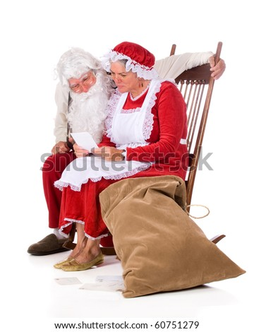 Mr. and Mrs. Santa Claus reading the kids' mail.  Isolated on white. - stock photo