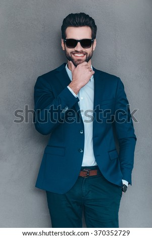 Mr. Handsome. Cheerful young handsome man in sunglasses keeping hand on chin and looking at camera with smile while standing against grey background - stock photo