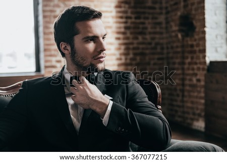 Mr. Handsome. Close up thoughtful young handsome man in formalwear and bow tie looking away and adjusting his bow tie while sitting in a chair in loft interior - stock photo