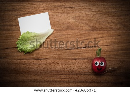 Mr. Radish is smiling and looking at the blank card, next are the lettuce on wooden table. Close-up view from above, image vignetting and the hard tones - stock photo
