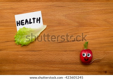 Mr. Radish is smiling and looking at the card with the word 'HEALTH', next are the lettuce on wooden table. Close-up view from above - stock photo