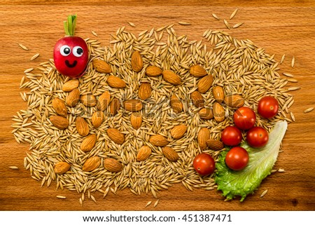 Mr. Radish is smiling and looking at the corns and almonds with cherry tomatoes on wooden table. Close-up view from above - stock photo
