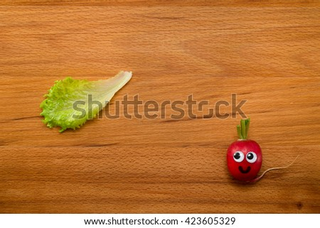 Mr. Radish is smiling and looking at the lettuce on wooden table. Close-up view from above - stock photo