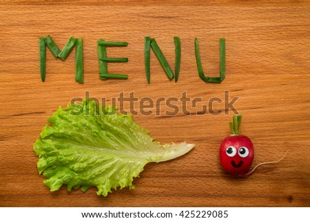 Mr. Radish is smiling and looking at the onion petals folded in the form of the word 'MENU' and lettuce on wooden table. Close-up view from above - stock photo