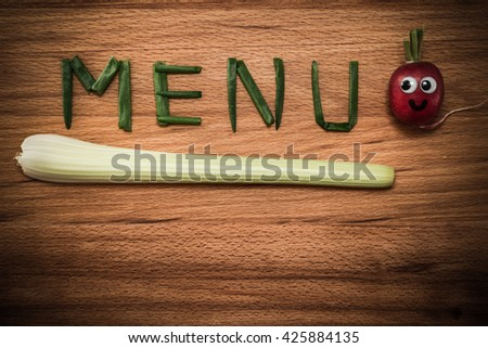 Mr. Radish is smiling and looking at the onion petals folded in the form of the word 'MENU' and celery on wooden table. Close-up view from above, image vignetting and the hard tones - stock photo