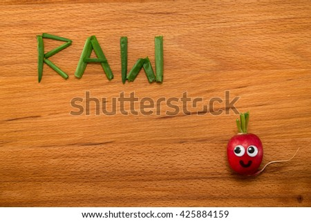 Mr. Radish is smiling and looking at the onion petals folded in the form of the word 'RAW' on wooden table. Close-up view from above - stock photo