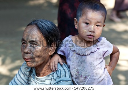 MRAUK U, MYANMAR - JANUARY 04: An unidentified Chin tribe tattooed woman and her granddaughter U Lihn, 5, posing for a photo during the Manaw Festival on January 04, 2012 in Mrauk U, Myanmar.