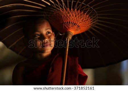MRAUK U, MYANMAR - JANUARY 18: Unidentified novice monk with red umbrella in buddhist temple on January 18, 2016 in Mrauk U, Myanmar - stock photo