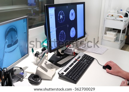 MRI scan of brain on Monitor in control room and and monitoring patient - stock photo