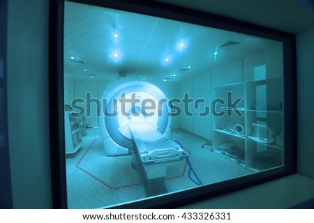 MRI scanner room in hospital take with art lighting and blue filter - stock photo