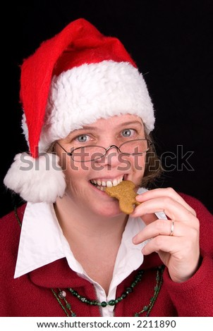 Mrs. Santa Claus bites a gingerbread cookie.....mmmmmmmmm, Christmasy - stock photo