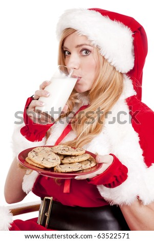 Mrs Santa has a plate of cookies and is drinking some milk. - stock photo