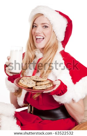 Mrs Santa is holding a plate of cookies and a glass of milk smiling. - stock photo