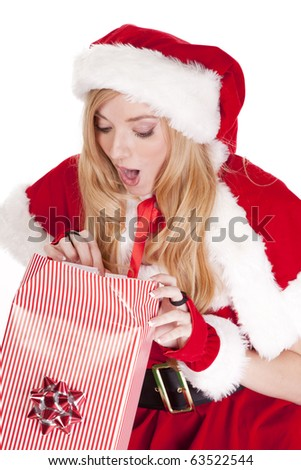 Mrs santa is opening a gift with a surprised expression on her face. - stock photo