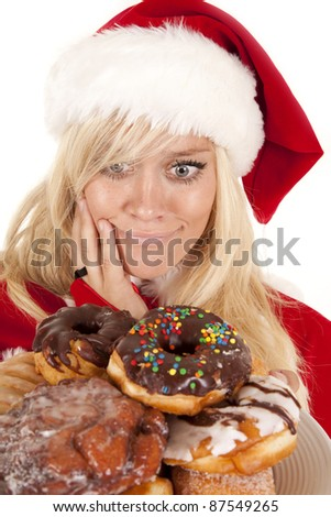 Mrs. Santa looking at a plate full of doughnuts not sure which one to eat. - stock photo
