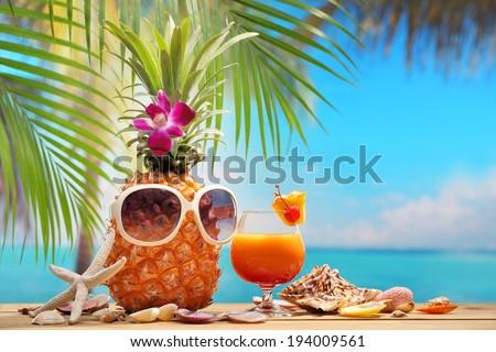 Ms ananas and a cup of cocktail on beach table - stock photo
