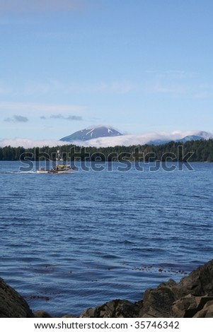Mt. Edgecumbe volcano near Sitka, Alaska with a fishing boat - stock photo