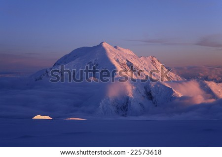 Mt. Foraker above a sea of clouds, lit up by the arctic's midnight sun, as seen from Denali, Denali National Park, Alaska. - stock photo