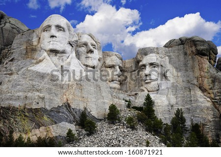 Mt. Rushmore National Memorial Park in South Dakota with bright blue sky in background. Sculptures of former U.S. presidents; George Washington,Thomas Jefferson,Theodore Roosevelt and Abraham Lincoln. - stock photo