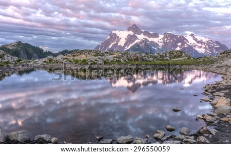 Mt Shuksan and colorful sunset clouds reflected in a tarn on Artist Ridge in Mt. Baker-Snoqualmie National Forest, Washington. - stock photo