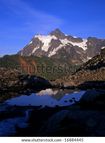 Mt. Shuksan, in North Cascades National Park, reflecting in a small pool, photographed from the Mt. Baker Wilderness Area in Washington State. - stock photo