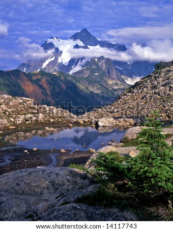 Mt. Shuksan reflecting in a pool of water in the Mount Baker Wilderness Area of Washington State. - stock photo