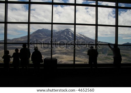 Mt. St. Helenes visitors peering through observation window - stock photo