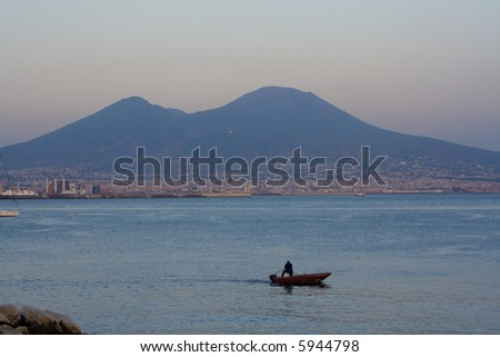 Mt.Vesuvius an active volcano near the city of Naples,Italy,view from Naples at dusk.A boat chugs along the Bay of Naples.The volcano is a realistic threat for about 3 million people living in Naples.