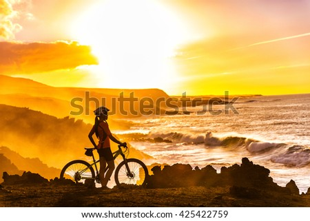 MTB cyclist mountain biking woman cycling looking at view on bike trail on coast at sunset. Person on bike by sea in sportswear with bicycle enjoying healthy active lifestyle in beautiful nature. - stock photo