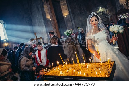 Mtskheta, Georgia - April 26, 2015. Young bride lights offering candle in the Holy Cross Monastery of Jvari near Mtskheta, one of the oldest cities of Georgia