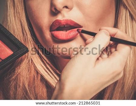 Mua artist painting red lips with tassel - stock photo
