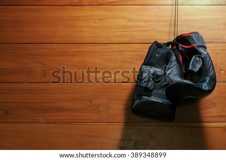 Muay Thai boxing gloves hanging on wooden wall  - stock photo