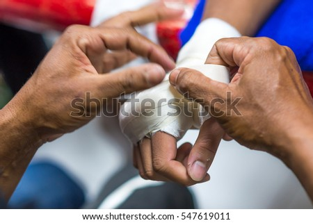 Muay Thai fighter putting bandage on the hands preparing to fight