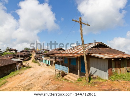 Mud bare earth village lane with wooden huts with corrugated sheet iron metal roofs and wooden makeshift electricity pole. A golden temple stupa at the end. - stock photo