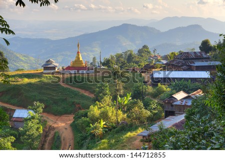 Mud bare earth village with wooden huts with corrugated sheet iron metal roofs and golden temple stupa at the end. - stock photo