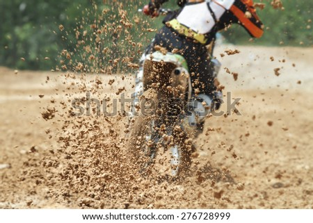 Mud debris flying from a motocross race - stock photo