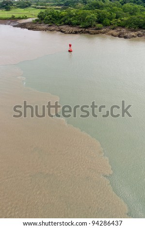 Mud disturbed by ships transiting the Culebra Cut on the Panama Canal - stock photo