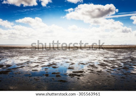 Mud flat at low tide. North sea landscape with cloud sky.  Nature reserve and travel destination in Germany - stock photo