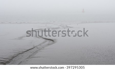 Mud is exposed on the River Mersey estuary at low tide in Liverpool during a winter fog. Birkenhead, usually visible across the water, is obscured by the fog. - stock photo