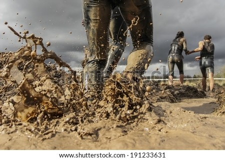 Mud race runner's muddy feet - stock photo