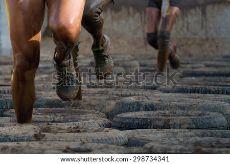 Mud race runners, tries to make it through the tire trap - stock photo