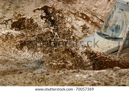 Mud spraying off an off road vehicle as it goes through a water hazard - stock photo