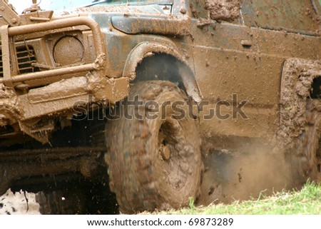 Mud spraying off the wheel of a vehicle competing in an off road rally - stock photo